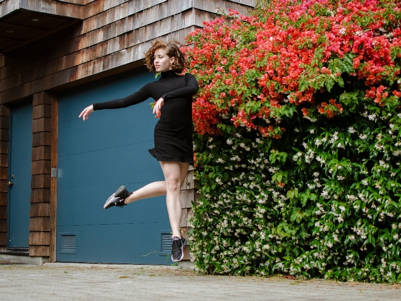 Brennan Wall jumping in front of a wall of bougainvillea, photo by Maggie Carey
