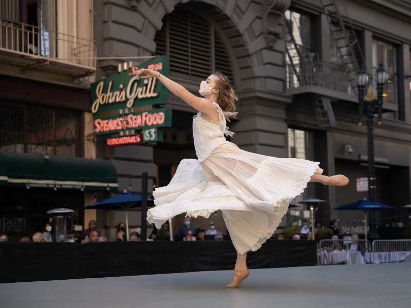 Cassidy Isaacson performing onstage in front of John's Grill in a flowing white dress, photo by Chris Hardy