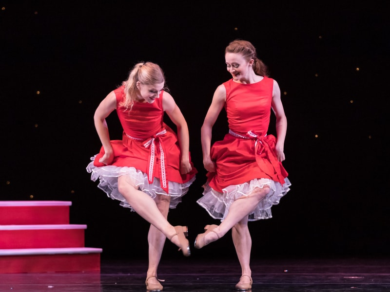 Maggie and Tessa clicking tap shoes together.