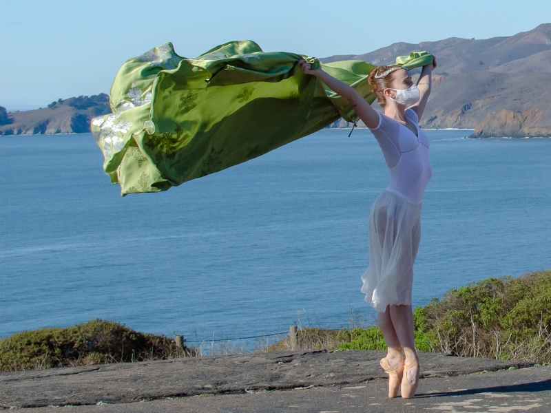 Maggie on pointe with green cape flying in the wind.
