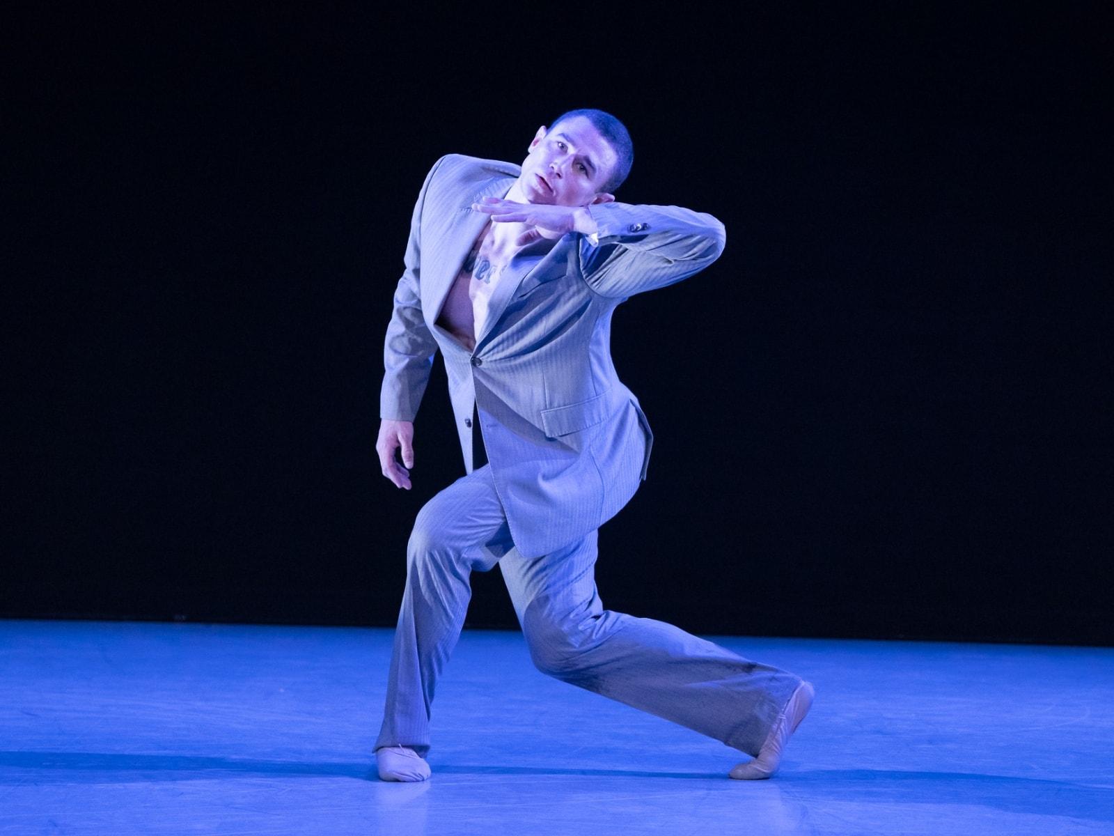 Max dancing in a grey suit.