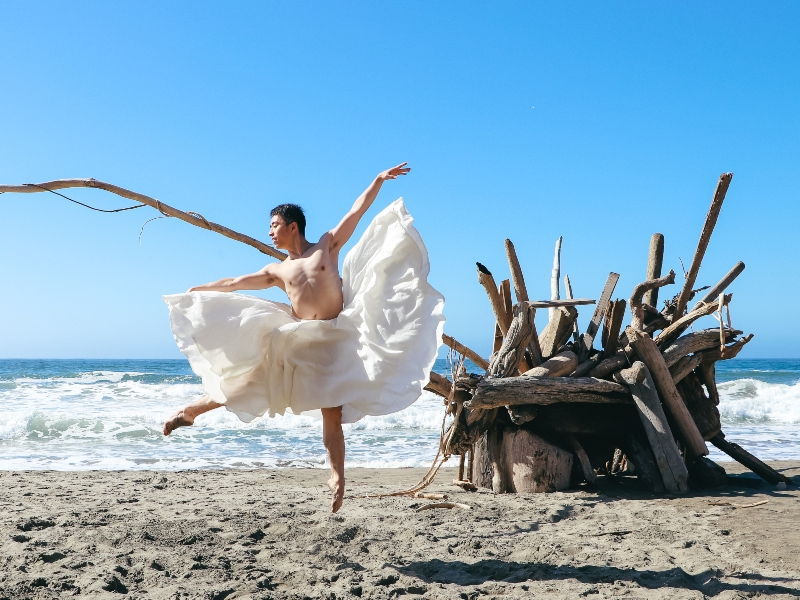 Meng dancing on the beach with a white dress on.