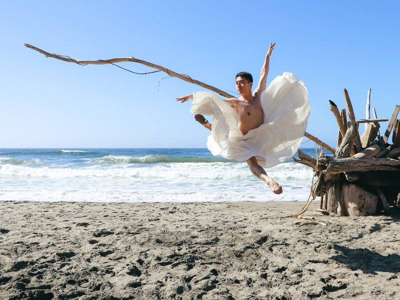 Meng jumping on the beach in a white dress.