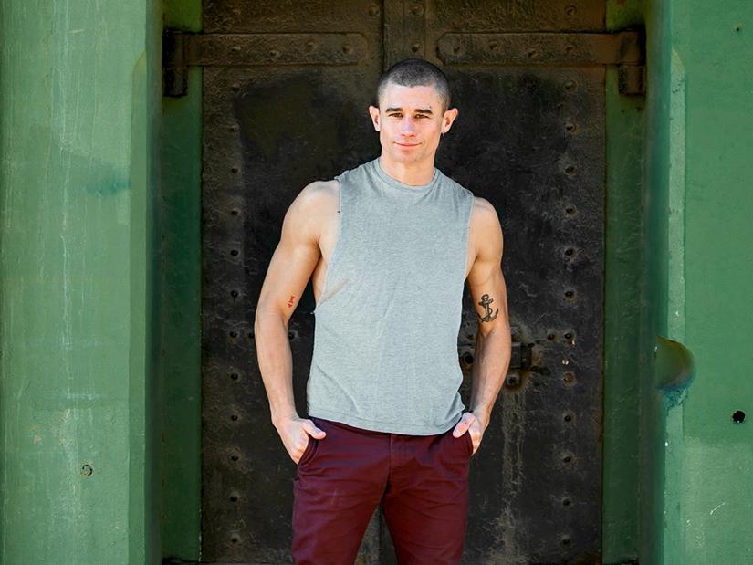 Max standing in front of old metal door.
