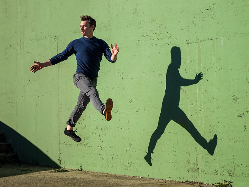 John jumping in front of a green wall.
