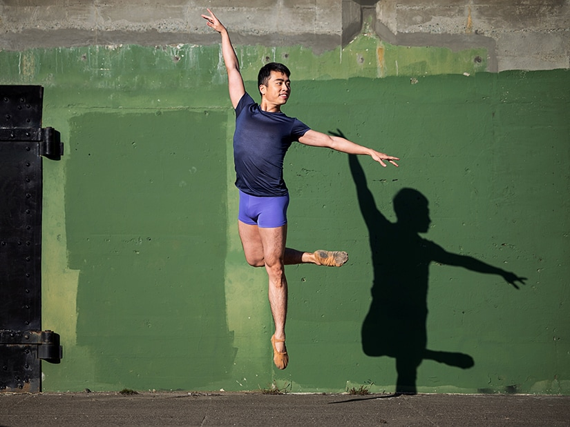Meng jumping outside in front of a green wall.