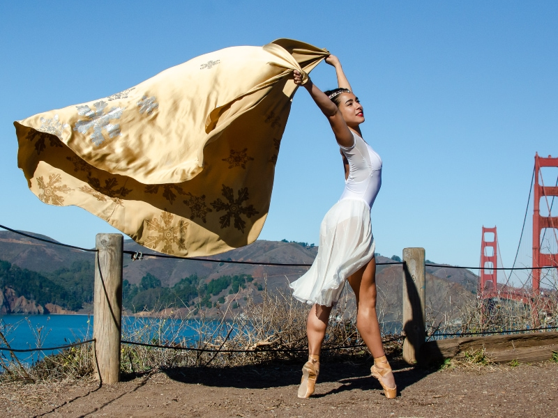 Tess dancing on pointe with gold cape blowing in the wind.