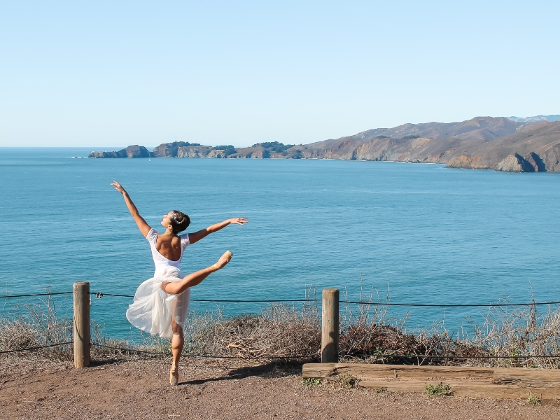 Tess on pointe with ocean in the background.
